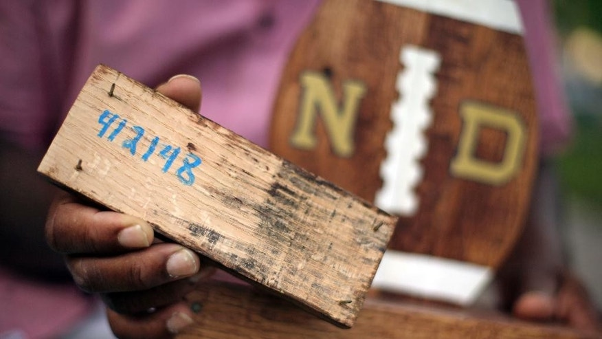 FILE - In this Aug. 14, 2015 file photo, Larry Stephney holds a piece of wood with the number 412148 written on it that is from a product made while he was an inmate at a privately run prison in Nashville, Tenn. The number refers to a section of Tennessee code that makes it illegal for jail officials to require an inmate to perform labor that results in the official's personal gain. Stephney says inmates were required to build plaques, birdhouses, dog beds and cornhole games for officials who sold the items through an online business and at a local flea market. Two Nashville jail employees and one former employee are charged with official misconduct, accused of pocketing money from the sale of inmate-made wooden plaques and games. (AP Photo/Mark Humphrey, File)
