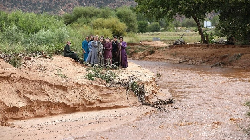 Community members look along a stream after a flash flood Tuesday, Sept. 15, 2015, in Colorado City, Ariz. Authorities have confirmed at least nine people have died in flash flooding that swept away two vehicles in Hildale, Utah, a town on the Utah-Arizona border. The floods came after heavy rains fell in the canyons just north of the sister towns of Hildale, Utah, and Colorado City, Arizona, sending waves of water barreling through the streets.  (AP Photo/Rick Bowmer)