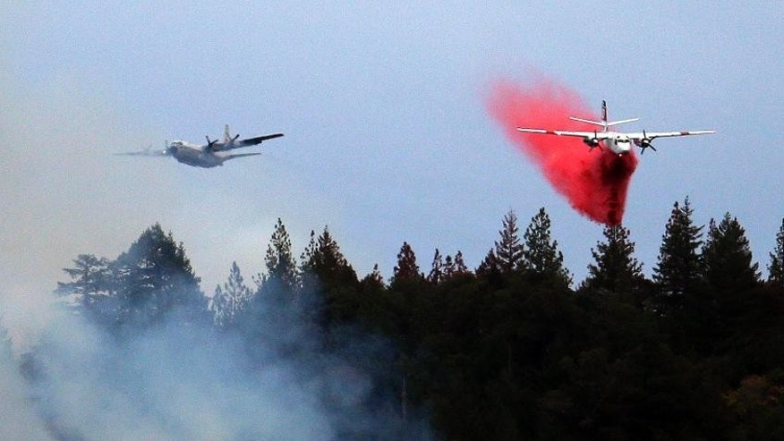 A firefighting plane is followed by another as it drops a load of fire retardant over a smoldering hillside Tuesday, Sept. 15, 2015, in Middletown, Calif. The fire that sped through Middletown and other parts of rural Lake County, less than 100 miles north of San Francisco, has continued to burn since Saturday despite a massive firefighting effort. (AP Photo/Elaine Thompson)