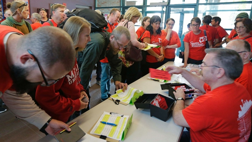 Sept. 15, 2015: Members of the Seattle Education Association, the union that represents striking teachers from the Seattle School District, sign in to receive voting cards as they arrive at a meeting hall in Seattle to discuss a tentative contract agreement that was reached with the district Tuesday morning, the fifth day of the strike.