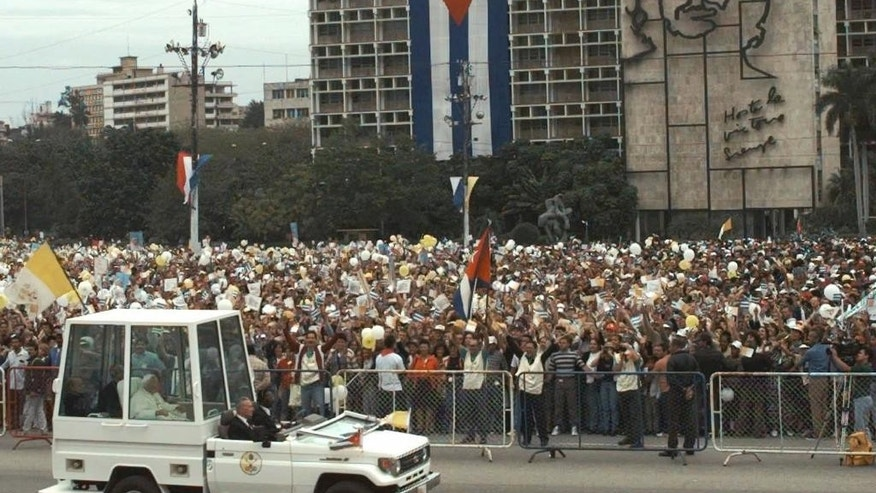 "FILE - In this Jan. 25, 1998 file photo, Pope John Paul II arrives to Plaza of the Revolution to celebrate Mass in Havana, Cuba, to celebrate Mass, where a  sculpture of Cuban revolutionary hero Ernesto ""Che"" Guevara covers the Interior Ministry building. Seventeen years ago, a newly named Argentine archbishop laid out his thoughts on the meaning of a papal visit to Cuba. ""Through the presence, the voice and the prophetic mission of the pope, the church offers a path forward to peace, justice and true liberty,"" Jorge Mario Bergoglio wrote. ""Not everything will be the same after he leaves."" Millions of Cubans hope those words written about John Paul II's 1998 trip to Cuba prove true when their author, now Pope Francis, flies into Havana on Saturday, Sept. 19, 2015. (AP Photo/Joe Cavaretta, File)"