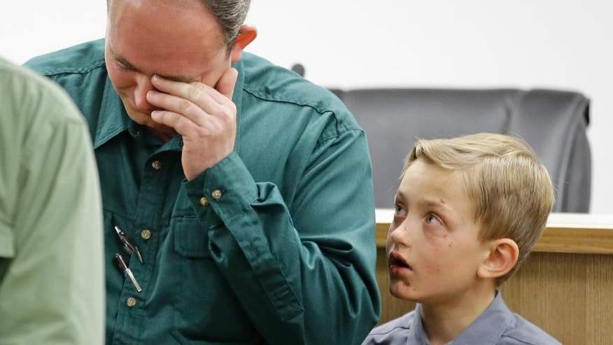 Sheldon Black, Jr., lowers his head as one of his two surviving sons looks on during a news conference Thursday, Sept. 17, 2015, in Colorado City, Ariz.  Black expressed his gratitude for the outpouring of support after his wife and children were swept away in a flash food Monday. (AP Photo/Rick Bowmer)
