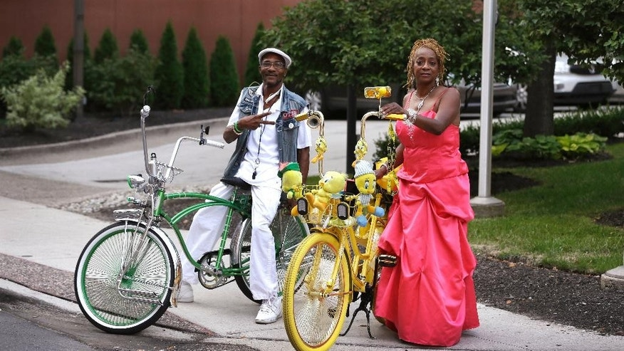 In a photo from Aug. 31, 2015, Dr. Cosmo and Velma Massey stand with their bicycles in the Greektown area of Detroit. Move aside Motor City. Make way for a new export that is turning Detroit's auto legacy on its wheels. Thousands of bicyclists hit the streets Monday evenings from spring to fall for Slow Roll Detroit, an ultracasual 10 mile or so tour of its best and blighted neighborhoods at speeds up to 10 mph. (AP Photo/Carlos Osorio)