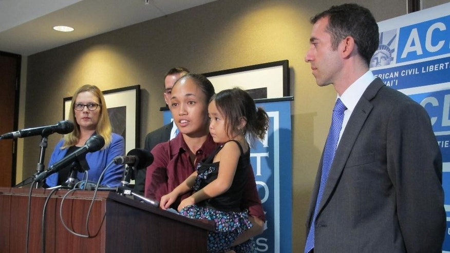 Tabatha Martin, center, talks to the media while holding her 4-year-old daughter, Thalia, as attorney Kristin Holland, left, and Dan Gluck, legal director of the American Civil Liberties Union Hawaii, right, listen Wednesday, Sept. 16, 2015, in Honolulu. Martin is among the plaintiffs in a lawsuit the ACLU filed Wednesday against the city of Honolulu, claiming city officials deprived homeless people of food and other belongings during raids on encampments. (AP Photo/By Cathy Bussewitz)