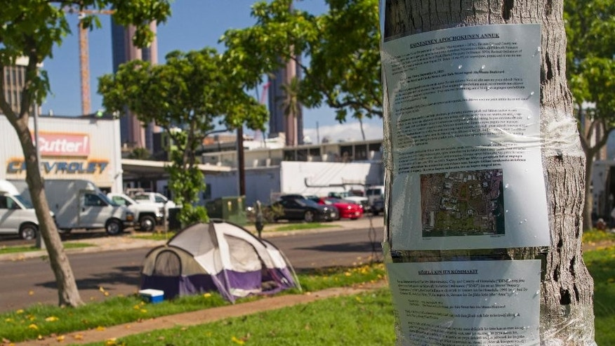 FILE - In this Sept. 8, 2015 file photo, signs posted in Chuukese and Marshallese announcing the beginning of sidewalk nuisance and stored property enforcement  are posted to a palm tree in Kaka'ako Park in Honolulu.  Attorneys with the American Civil Liberties Union say the group will sue Honolulu over the way city officials are clearing out homeless encampments. The attorneys say they plan to file a lawsuit Wednesday, Sept. 16, 2015. (AP Photo/Marco Garcia)
