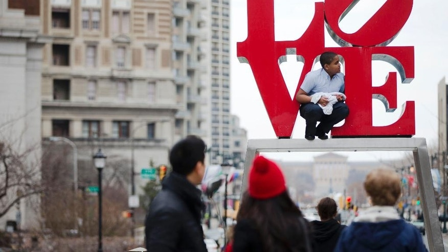 "FILE - In this March 27, 2015, file photo, a young man climbs on a sculpture by Robert Indiana, at JFK Plaza, commonly known as Love Park, in Philadelphia. A bilingual version of Maine-based pop artist  Indiana's ""LOVE"" sculpture called the ""AMOR"" is going on display outside the Philadelphia Museum of Art, near where the pope's altar is being built. (AP Photo/Matt Rourke, File)"
