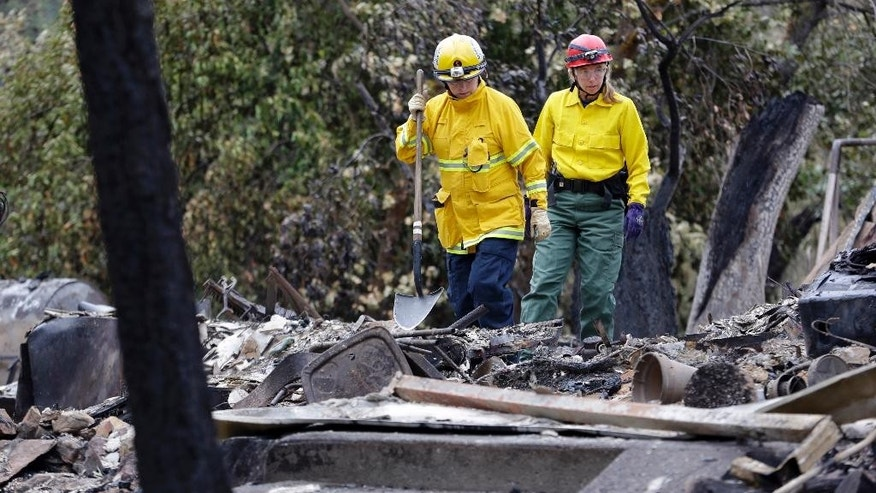 Cadaver search dog handlers Lynne Engelbert, left, and Mary Cablk look over the remains of a home in the Anderson Springs area of a man missing following a wildfire days earlier before bringing their dogs through Wednesday, Sept. 16, 2015, near Middletown, Calif. Aided by drought, the flames have consumed more than 100 square miles since the fire sped Saturday through rural Lake County, less than 100 miles north of San Francisco. Cooler weather helped crews gain ground and the fire was 30 percent contained Wednesday. (AP Photo/Elaine Thompson)
