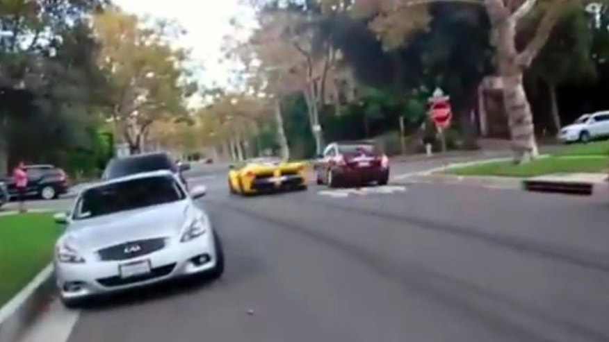 This frame grab from a video shows a yellow Ferrari speeding through a stop sign, Thursday, Sept. 17, 2015, in Beverly Hills, Calif. A Middle Eastern sheikh who allegedly said he owned a Ferrari caught on film speeding through a Beverly Hills neighborhood apparently has raced out of town, police said Thursday. Khalid bin Hamad Al Thani of Qatar has left the country and the cars are gone, authorities said at a news conference. (AP Photo)