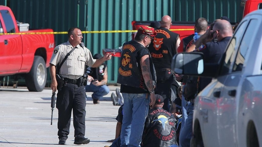 FILE - In this May 17, 2015 file photo, authorities investigate a shooting in the parking lot of the Twin Peaks restaurant in Waco, Texas. Police shot bikers in the deadly shootout that erupted last spring outside a Texas restaurant, though it remains unclear if their bullets caused any of the nine fatalities, according to evidence reviewed by The Associated Press. (AP Photo/Jerry Larson, File)