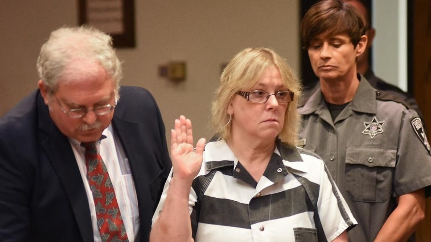"FILE - In this July 28, 2015 file photo, Joyce Mitchell raises her hand during a court appearance in Plattsburgh, N.Y.  Mitchell, the former New York prison employee who helped two killers escape from a maximum-security prison in June, said in an interview that aired Monday, Sept. 14, on NBC's ""Today"" show that she was depressed at the time and the inmates took advantage of what she called her ""weakness."" (Rob Fountain/The Press-Republican via AP, Pool, File)"