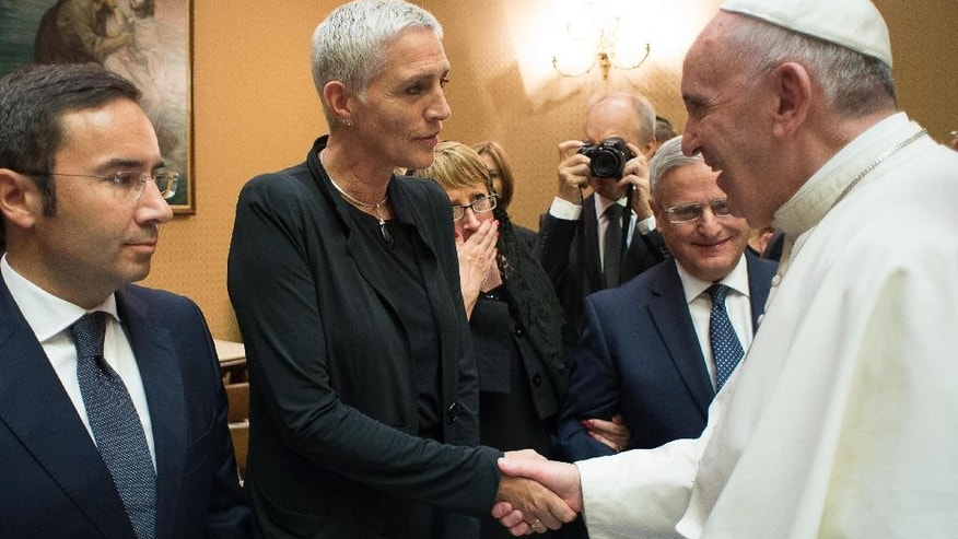 In this picture taken on Sept. 16, 2015 and made available on Sept. 17, 2015, Pope Francis shakes hands with Dutch State Secretary for the Ministry of Infrastructure and the Environment, Wilma Jacqueline Mansveld, second left, during a meeting with European Union Environment ministers at the Vatican. (L'Osservatore Romano/Pool Photo via AP)