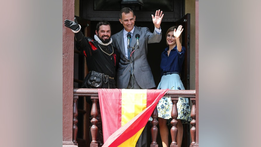 King Felipe VI of Spain, accompanied by Queen Letizia and Chad Light, left, portraying historic figure Pedro Menendez, wave to a crowd from the balcony of Governors House in St. Augustine as part of the city's 450th Commemoration, Friday, Sept. 18, 2015, St. Augustine, Fla. (AP Photo/Gary McCullough)