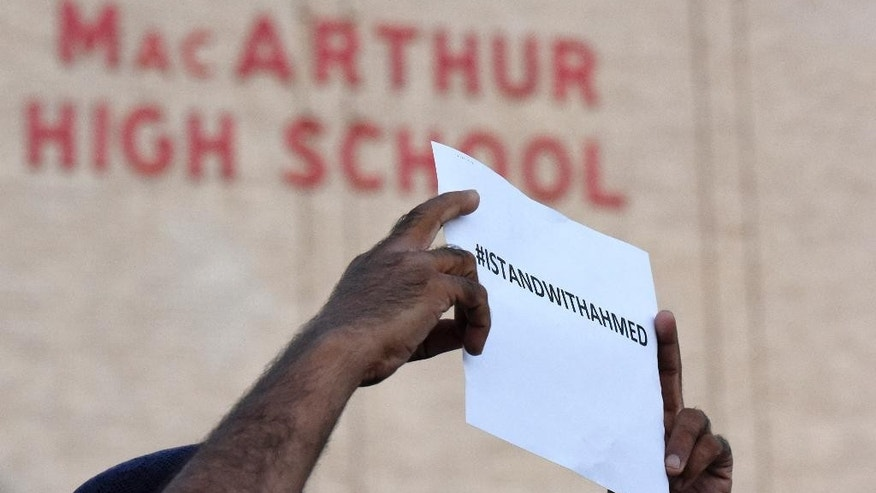 A sign supporting Ahmed Mohamed is held up in front of MacArthur High School at a prayer vigil, Thursday, Sept. 17, 2015, in Irving, Texas.  Ahmed, 14, was arrested Monday when a clock he built and brought to school was mistaken for a bomb by teachers and police.  (AP Photo/Jeffrey McWhorter).