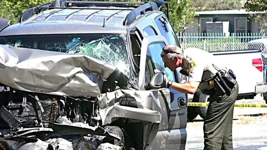 A deputy checks an SUV involved in a crash on Interstate 215 at the Little League Drive freeway overpass in San Bernardino, Calif., Friday, Sept. 18, 2015. Authorities say a wrong-way freeway driver has died in California after being shot at from a San Bernardino County sheriff's helicopter during a chase. (Richard Brooks/The Press-Enterprise via AP) MAGAZINES OUT; MANDATORY CREDIT; LOS ANGELES TIMES OUT