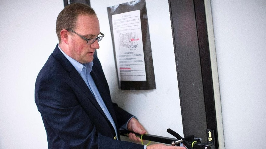 FILE - In this file photo taken on Monday, July 20, 2015, Ben Richards, principal of Watkins Memorial High School, demonstrates the use of a security device in Pataskala, Ohio. School security and fire safety experts are questioning a nationwide push allowing schools to buy portable barricade devices, saying the devices may be complicated to install under stress and could lead to dangerous unintended consequences, including blocking authorities from an attacker inside a classroom. (AP Photo/John Minchillo, File)