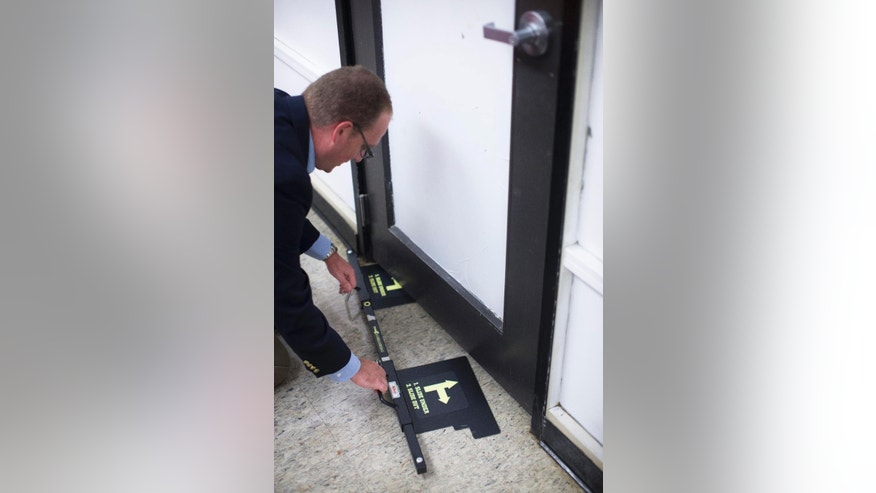 FILE - In this file photo taken Monday, July 20, 2015, Ben Richards, principal of Watkins Memorial High School, demonstrates the use of a security device in Pataskala, Ohio. School security and fire safety experts are questioning a nationwide push allowing schools to buy portable barricade devices, saying the devices may be complicated to install under stress and could lead to dangerous unintended consequences, including blocking authorities from an attacker inside a classroom. (AP Photo/John Minchillo, File)