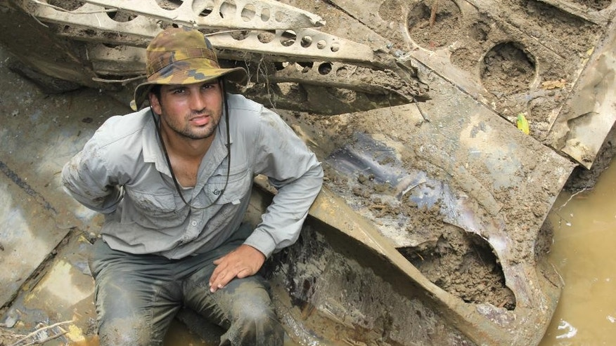 In this 2014 photo provided by Pacific Wrecks, Justin Taylan, founder and director of Pacific Wrecks poses at a World War II airplane wreck site in Papua New Guinea (PNG). Taylan founded Pacific Wrecks 20 years ago after visiting crash sites and battlefields with his grandfather, a WWII veteran. Since then, the 37-year-old Hyde Park, N.Y., native has visited PNG dozens of times to search its dense jungles for wreck sites and is wrapping up a two-year contract with the Pentagon to help find the remains of Americans still listed as missing in action there. (Marcus Browning/Pacific Wrecks via AP)