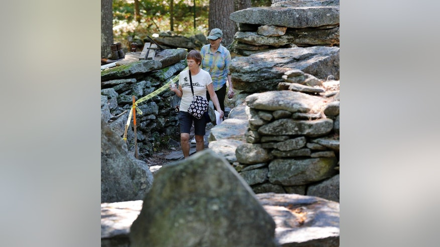 In this photo taken Tuesday, Sept. 15, 2015, Marie St. Onge, left, and Carol Stevens walk through what is called America's Stonehenge, in Salem, N.H. The 1-acre grouping of rock configurations has drawn believers to say it is thousands of years old. Skeptics say the evidence suggests it was put together by a 19th century shoemaker. (AP Photo/Jim Cole)