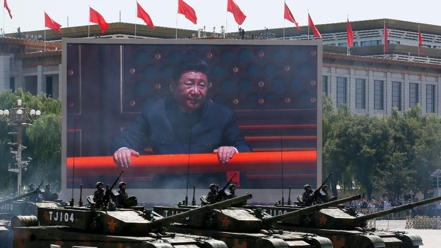 FILE - In this Sept. 3, 2015 file photo, Chinese President Xi Jinping is displayed on a big screen as Type 99A2 Chinese battle tanks roll across during a parade commemorating the 70th anniversary of Japan's surrender during World War II in Beijing. As Xi makes his first state visit to Washington this week, the outlook for relations is decidedly murkier than when he hosted President Barack Obama at their last summit less than a year ago. Xi presided over the massive military parade that showcased the growing might of the People's Liberation Army. The event was a hit among the Chinese public, but it was criticized abroad as threatening in appearance and unhelpful to reconciliation with World War II antagonist Japan. (AP Photo/Ng Han Guan, File)