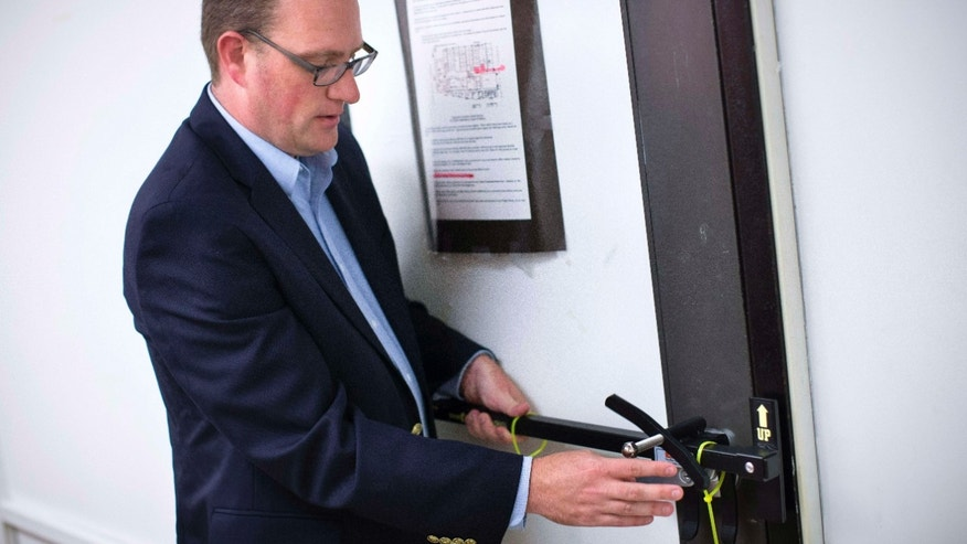 FILE - In this file photo taken on Monday, July 20, 2015, Ben Richards, principal of Watkins Memorial High School, demonstrates the use of a security device in Pataskala, Ohio.