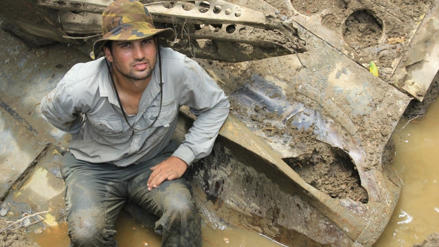 In this 2014 photo provided by Pacific Wrecks, Justin Taylan, founder and director of Pacific Wrecks poses at a World War II airplane wreck site in Papua New Guinea (PNG).