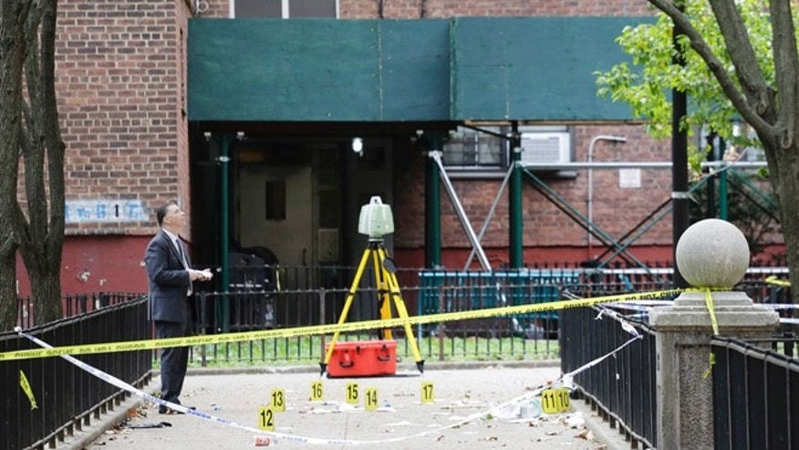 A New York City crime scene investigator inspects the scene of a triple homicide in Brooklyn.