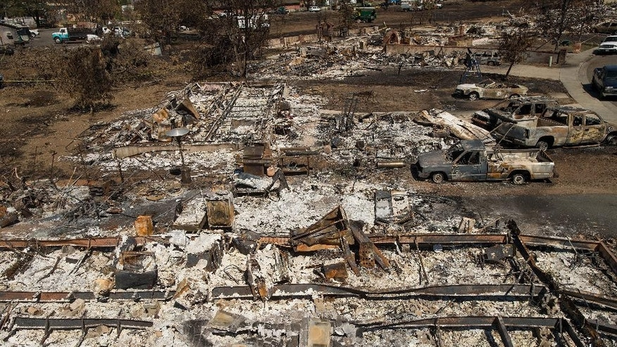 Destroyed homes and vehicles scorched by the Valley fire line Jefferson St. in Middletown, Calif, on Monday, Sept. 21, 2015. According to fire officials, the blaze ranks as the sixth worst wildfire in California history after destroying more than 1,000 structures, burning more than 75,000 acres and leaving at least three people dead. (AP Photo/Noah Berger)