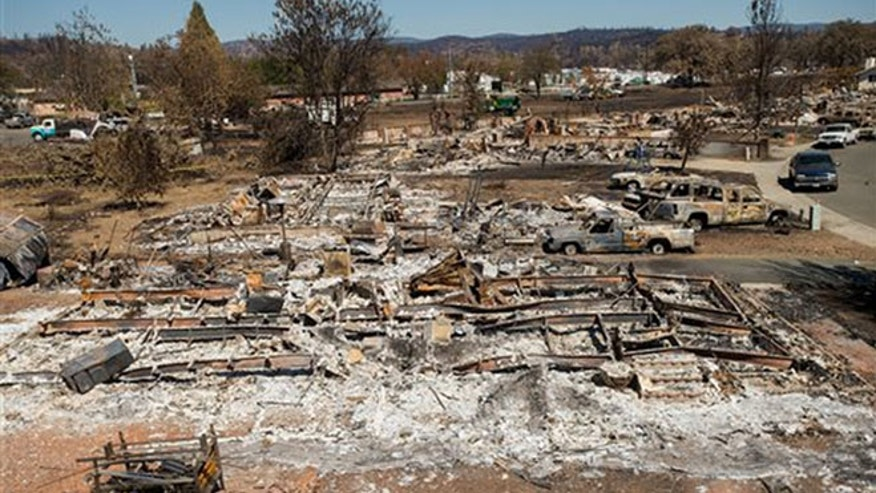 Destroyed homes and vehicles scorched by the Valley fire line Jefferson St. in Middletown, Calif, on Monday, Sept. 21, 2015. (AP Photo/Noah Berger)