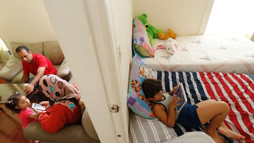 In this photo taken Wednesday, Sept. 16, 2015, Wesam Alroustom, right, plays on a tablet as his father, Hussam, top left, and his mother, Suha, center, play with his sister Maaesa in their apartment in Jersey City, N.J. Wesam, who is autistic, is a Syrian refugee after his family fled their war stricken country. (AP Photo/Julio Cortez)