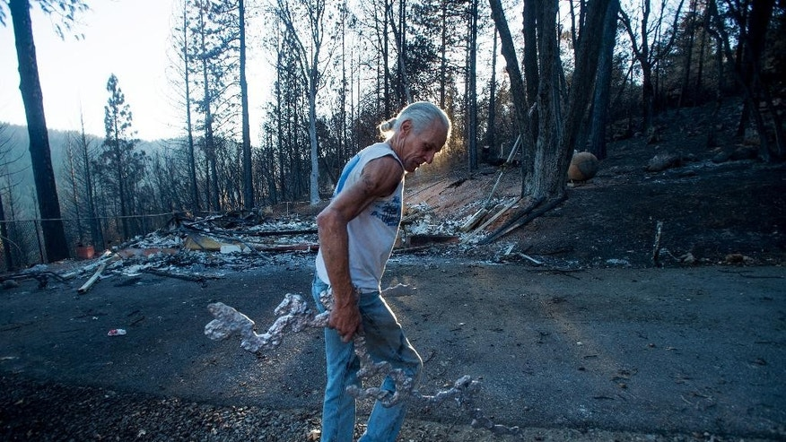 J.D. Roel salvages a scrap of melted metal from a friend's property after a wildfire raged through the Loch Lomond area of Lake County, Calif., Monday, Sept. 21, 2015. Gov. Jerry Brown requested a presidential disaster declaration on Monday, noting that more than 1,000 homes had been confirmed destroyed, with the number likely to go higher as assessment continues. (AP Photo/Noah Berger)