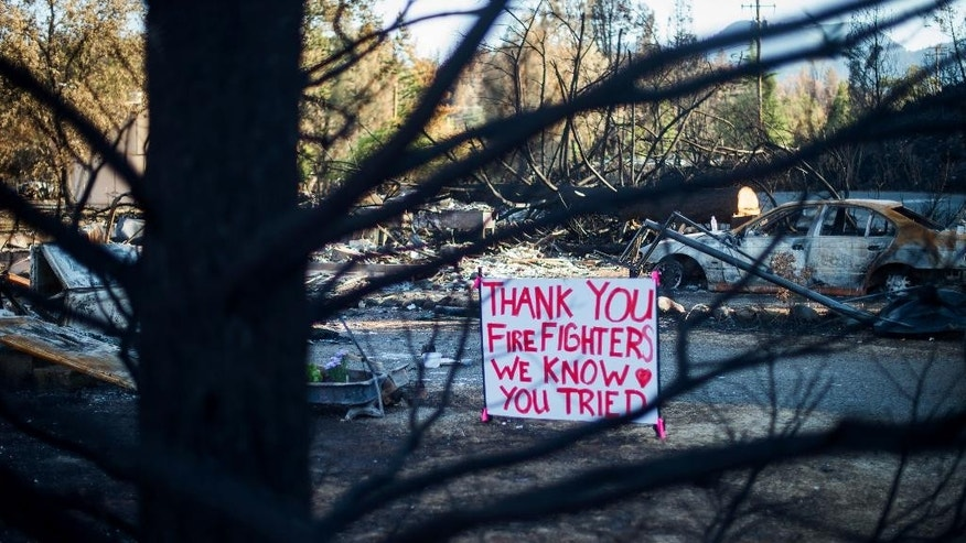 In front of a home destroyed by a wildfire, a sign displays a message of thanks for firefighters in Middletown, Calif., Monday, Sept. 21, 2015. Gov. Jerry Brown requested a presidential disaster declaration on Monday, noting that more than 1,000 homes had been confirmed destroyed, with the number likely to go higher as assessment continues. (AP Photo/Noah Berger)