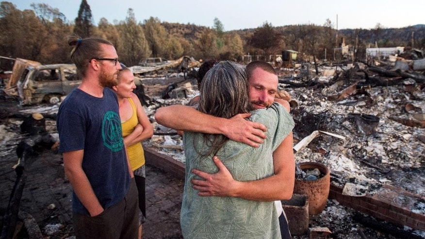 Charlie Liethen, right, embraces Sharon Dawson, who lost her home in a wildfire, in Middletown, Calif., Monday, Sept. 21, 2015. Gov. Jerry Brown requested a presidential disaster declaration on Monday, noting that more than 1,000 homes had been confirmed destroyed, with the number likely to go higher as assessment continues. (AP Photo/Noah Berger)