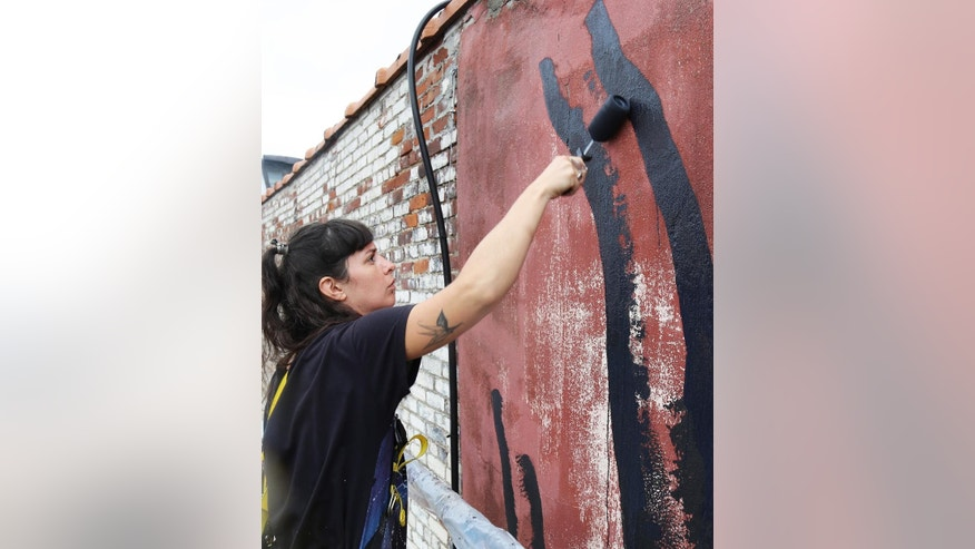 "In this Sept. 10, 2015 photo, Argentine artist Marina Zumi paints a large gazelle mural on the side of a New York building. Maziar Bahari, the journalist who spent 118 days in an Iranian jail after an appearance on ""The Daily Show with Jon Stewart,"" and later immortalized in Stewart's film ""Rosewater"" is using his newfound fame to create campaign called ""Not a Crime,"" which focuses on journalism and access to education for Iran's largest religious minority, the Baha'i. Part of the outreach effort involves murals painted across New York City. (AP Photo/Mike Balsamo)"