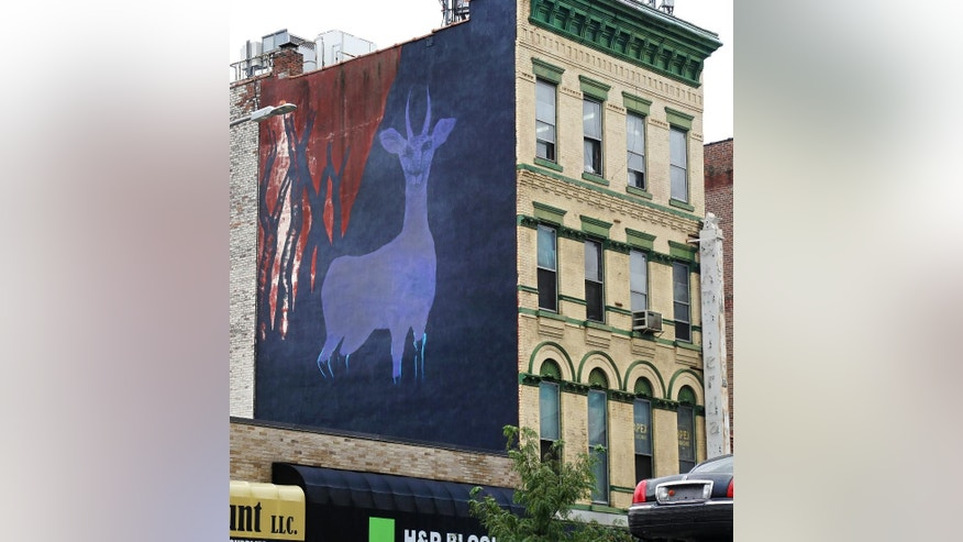 "In this Sept. 10, 2015 photo, a mural by artist Marina Zumi is seen on the side of a building in New York City. Maziar Bahari, the journalist who spent 118 days in an Iranian jail after an appearance on ""The Daily Show with Jon Stewart,"" is using his newfound fame to create campaign called ""Not a Crime,"" which focuses on journalism and access to education for Iran's largest religious minority, the Baha'i. (AP Photo/Mike Balsamo)"