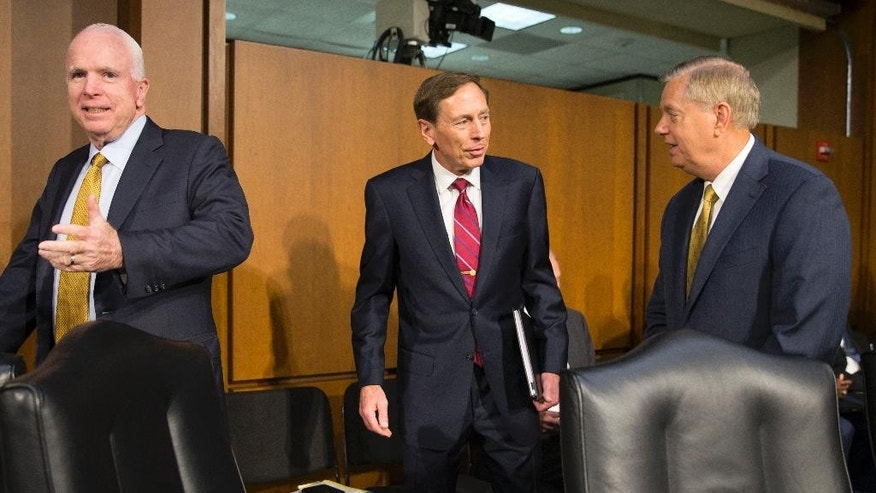 Former CIA Director David Petraeus, center, walks with Senate Armed Services Committee Chairman Sen. John McCain, R-Ariz., left, and Sen. Lindsey Graham, R-S.C., right, as he arrives on Capitol Hill in Washington, Tuesday, Sept. 22, 2015, to testify before the committee's hearing on Middle East policy. (AP Photo/Evan Vucci)