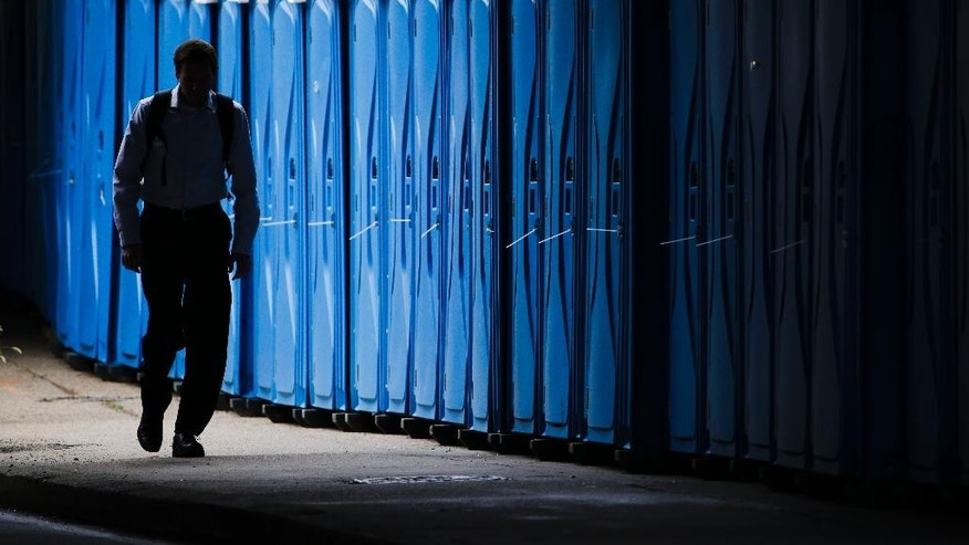A pedestrian walks past portable toilets staged ahead the World Meeting of Families and Pope Francis's scheduled visit, Tuesday, Sept. 22, 2015, in Philadelphia. Pope Francis will attend the World Meeting's closing concert, the Festival of Families, on Saturday and celebrate Mass on Sunday. Both events are being held on the city's Benjamin Franklin Parkway. Francis will parade down the parkway's outer lanes before both events. (AP Photo/Matt Rourke)