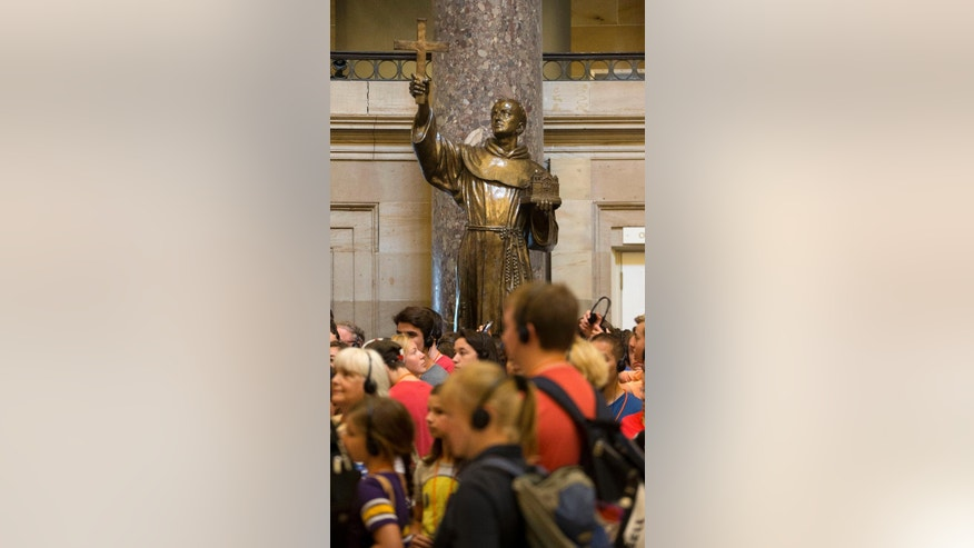 FILE - In this July 2, 2015, file photo, Capitol Hill visitors walk in front of a statue of missionary Junipero Serra, center, located in Statuary Hall, also known as the Old Hall of the House, on Capitol Hill in Washington. The first pope from the Americas is preparing to elevate to sainthood an 18th-Century missionary who brought Catholicism to California. Pope Francis will canonize Junipero Serra during a Mass on Sept. 23 outside the Basilica of the National Shrine of the Immaculate Conception in Washington.(AP Photo/Pablo Martinez Monsivais, File)