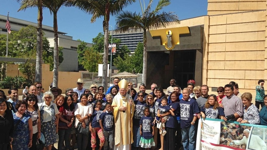 "Los Angeles Archbishop Jose Gomez, center, is surrounded by pilgrims outside the Cathedral of Our Lady of the Angels, Saturday, Sept. 19, 2015, in Los Angeles. Archbishop Gomez exalted Saint Junipero Serra as one of the ""founders of California"" and ""fathers"" of the United States, during a Mass in which he blessed dozens of pilgrims ahead of Pope Francis' visit to the U.S.  (AP Photo/Edwin Tamara)"