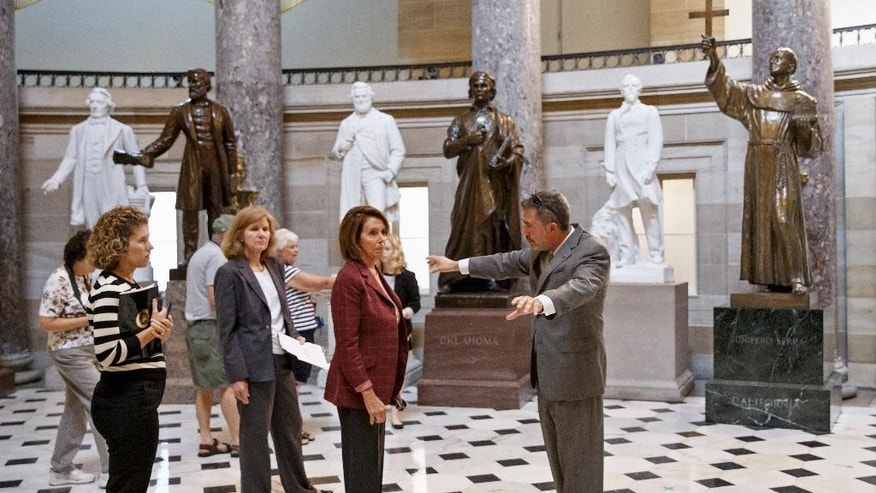 House Minority Leader Nancy Pelosi of Calif., center, gets a preview of Pope Francis' tour of the Capitol from Assistant Sergeant at Arms Ted Daniel, right, Friday, Sept. 18, 2015, in Statuary Hall on Capitol Hill in Washington. At far right stands a statue of Father Junipero Serra who founded Catholic missions in California in the 18th century. Father Serra will be canonized when the pope comes to Washington next week.  (AP Photo/J. Scott Applewhite)