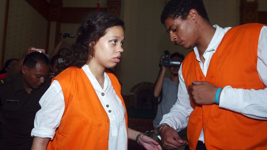 FILE - In this March 31, 2015 file photo, Heather Mack, 19, left, and her boyfriend Tommy Schaefer, 21, of Chicago, are handcuffed as they arrive at a courtroom during their trial in Bali, Indonesia.