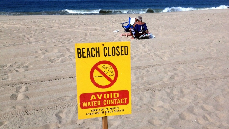 This Thursday, Sept. 24, 2015 photo provided by Matthew King shows beachgoers sit in the sand near a closed beach sign at El Segundo Beach in El Segundo, Calif.