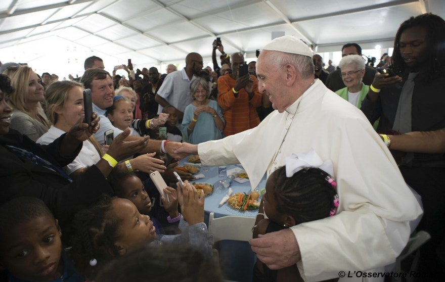 In this photo taken Thursday, Sept. 24, 2015, Pope Francis is greeted as he arrives at a lunch for homeless people who are regularly fed by Catholic Charities, at St. Patrick's Church in Washington, following his address to a joint meeting of Congress on Capitol Hill. (L'Osservatore Romano/Pool Photo via AP)