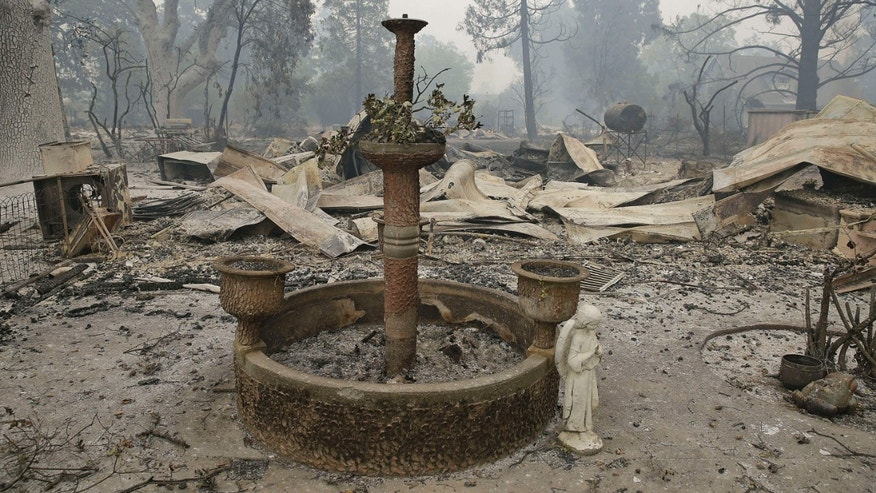Sept. 13, 2015: A fountain and statue of an angel stand outside a home destroyed by fire in Middletown , Calif.