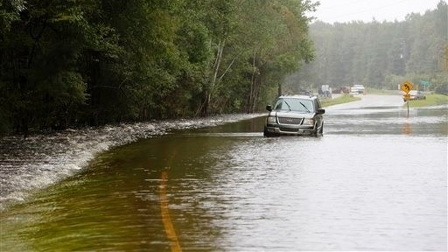 A vehicle is stranded on Cainhoy Road due to flood waters near Huger, S.C., Monday, Oct. 5, 2015. South Carolina is still struggling with flood waters due to a slow moving storm system. (AP Photo/Mic Smith)