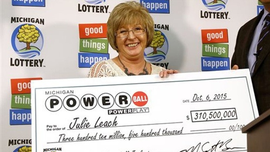 Oct 6, 2015: Powerball winner Julie Leach, of Three Rivers, Mich., holds a ceremonial check during a news conference at lottery headquarters in Lansing, Mich. Leach won $310.5 million in the Sept. 30 drawing.