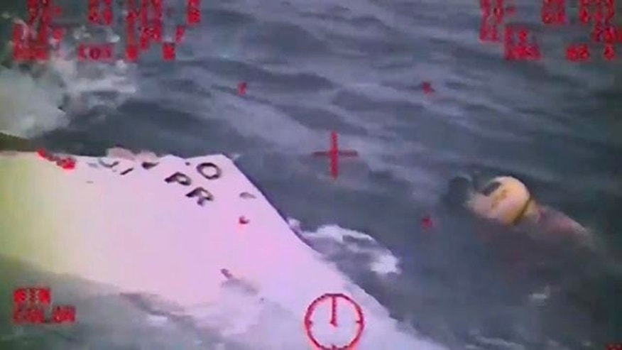 Oct. 4, 2015: In this photo made from video and released by the U.S. Coast Guard, a Coast Guard crew member investigates a life boat that was found from the missing ship El Faro. (U.S. Coast Guard via AP)