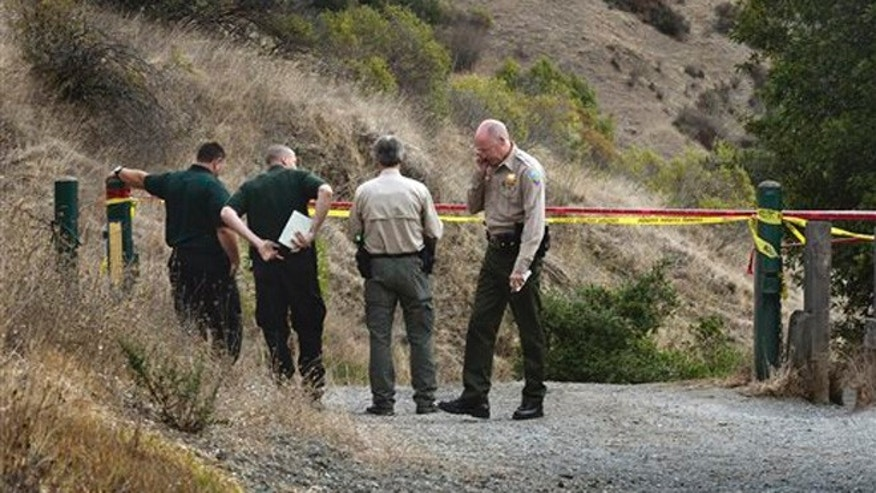 In this Tuesday, Oct. 6, 2015 photo, Marin County Sheriff's members investigate a homicide near the top of White's Hill on Old Railroad Grade near Fairfax, Calif.