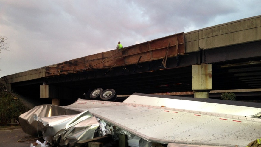 The wreckage of a tractor trailer lies under an overpass in Suitland, Md., Friday, Oct. 9, 2015. (Assistant Fire Chief Alan C. Doubleday/Prince Georges County, Md. Fire Department via AP)