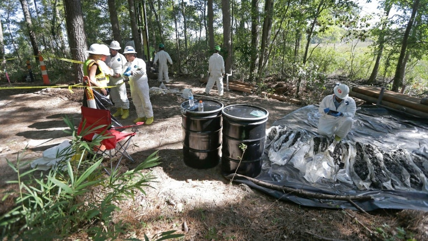 In this photo taken Tuesday, Sept. 15, 2015, contractors collect and inspect soil samples taken at a Superfund cleanup site in Navassa, N.C.