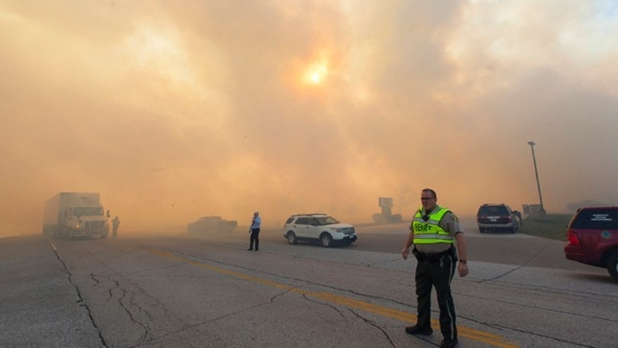 Oct. 12, 2015: Authorities direct traffic for vehicles passing through heavy smoke from a burning field in Eldridge, Iowa.